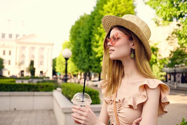 Vrouw in een hoed-account drankje buiten wandelen rond de stadsvakantie