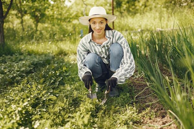 Vrouw in een hoed die in een tuin werkt