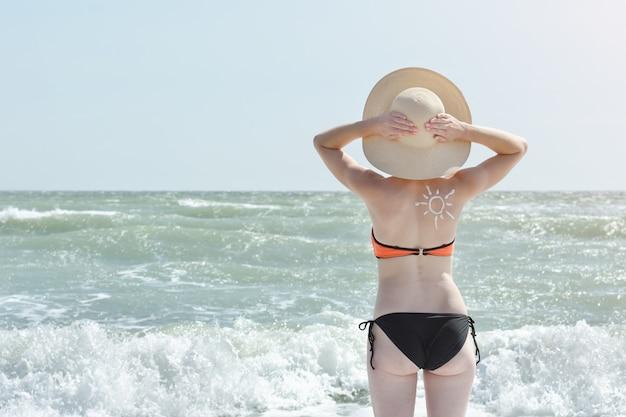 Vrouw in een hoed en een zwempak aan zee. achteraanzicht.