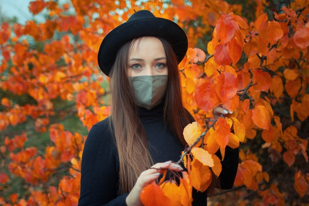 Vrouw in een hoed en masker over een herfstboom