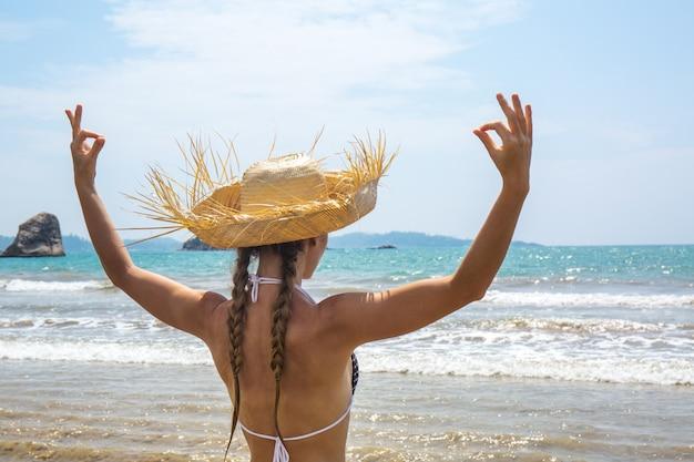 Vrouw in een hoed mediteert op de oceaan kust