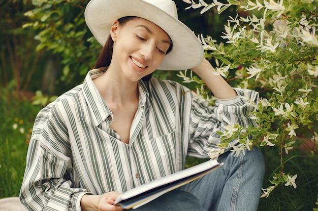 Vrouw in een hoed met een boek in een tuin