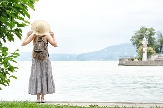Vrouw in een hoed met een rugzak staande op een pier aan de zee. bergen en vuurtoren op de achtergrond.