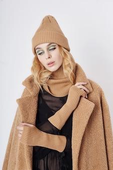 Vrouw in een jas, creatieve lentemake-up op haar gezicht. grote expressieve ogen van het meisje. warme kleding