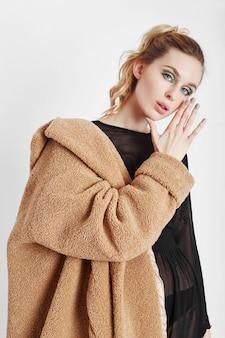 Vrouw in een jas, creatieve lentemake-up op haar gezicht. grote expressieve ogen van meisje. warme kleding