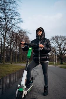 Vrouw in een jas op een elektrische scooter in een herfstpark.