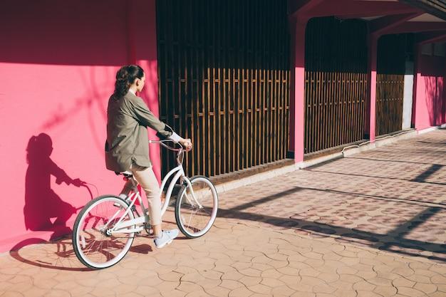 Vrouw in een jas rijdt op een stadsfiets