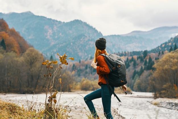 Vrouw in een jeans-trui met een rugzak rust in de bergen in de buurt van de rivier in de natuur
