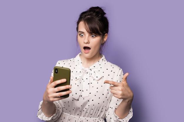 Vrouw in een jurk wijst verbaasd naar haar telefoonscherm