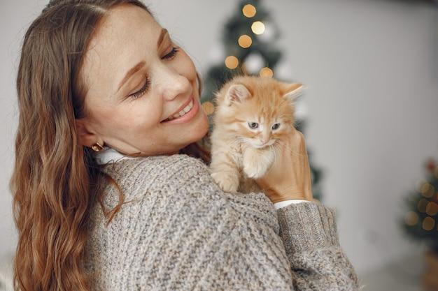 Vrouw in een kamer. persoon in een grijze trui. dame met klein katje.