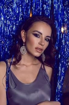 Vrouw in een korte jurk staat in de club voor de vakantie nieuwe jaar in sieraden blauwe linten