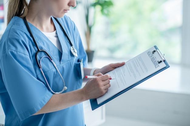 Vrouw in een laboratoriumjas die een ziekteverzekeringsovereenkomst ondertekent