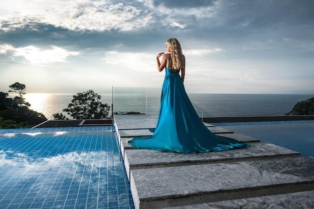 Vrouw in een lange blauwe avondjurk