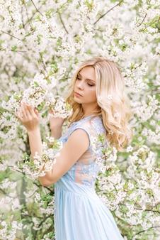 Vrouw in een lange blauwe jurk in een lentetuin. inschrijving foto met witte bloemen
