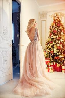Vrouw in een lange crèmekleurige jurk, staande bij de kerstboom en de deur. luxe blondine in een avondjurk die kerstmis en nieuwjaar viert