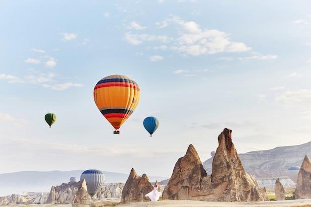 Vrouw in een lange jurk op de achtergrond van ballonnen in cappadocië