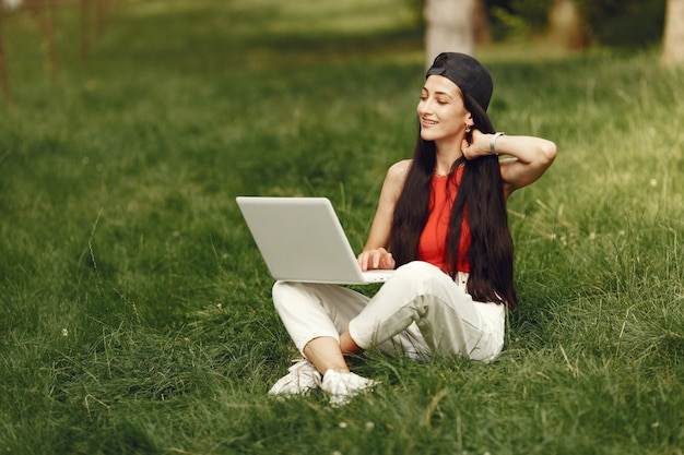 Vrouw in een lentestad. dame met een laptop. meisje zittend op een gras.
