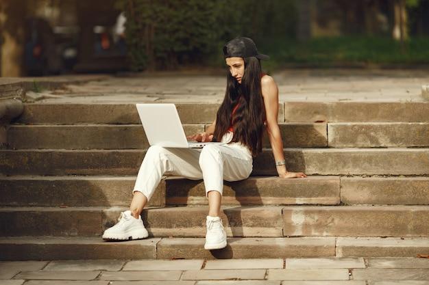 Vrouw in een lentestad. dame met een laptop. meisje zittend op een trap.