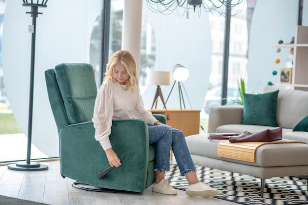 Vrouw in een lichte blouse zittend in een grote comfortabele stoel, met haar hand bij de hendel, aandachtig naar beneden te kijken.