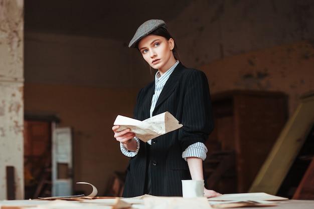 Vrouw in een mannelijke retro-look leest een brief