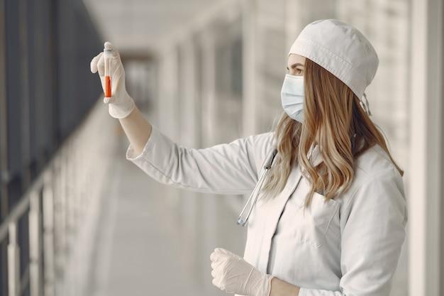 Vrouw in een masker en uniform met een buis in haar handen