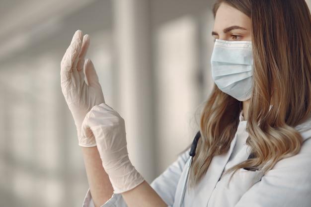 Vrouw in een masker en uniform zet op handschoenen