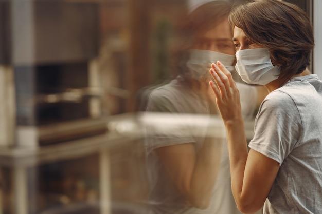 Vrouw in een masker staat bij het raam