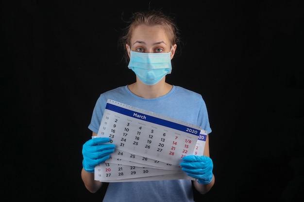 Vrouw in een medisch beschermend masker, handschoenen houden maandkalender op een zwarte muur. quarantaine, pandemische covid-19