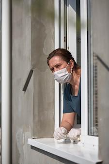 Vrouw in een medisch gezichtsmasker kijkt uit het raam.