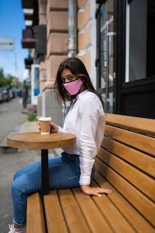 Vrouw in een medisch masker drinkt koffie op straat