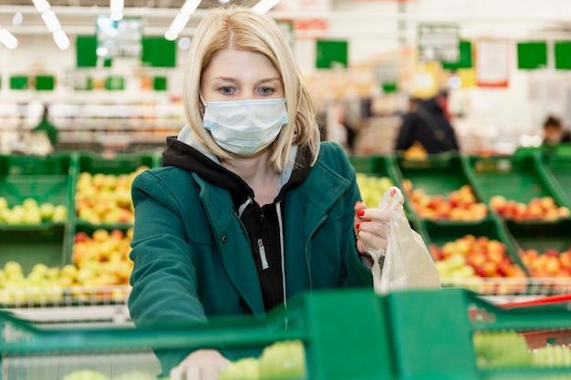 Vrouw in een medisch masker kiest groenten in een supermarkt. zelfisolatie bij een pandemie.