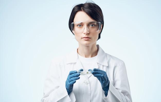 Vrouw in een medische jurk en glazen houdt een kolf met een plant in haar hand biologie plantkunde geneeskunde