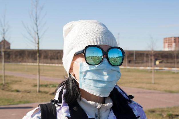 Vrouw in een medische pak en zonnebril op straat. coronavirus concept
