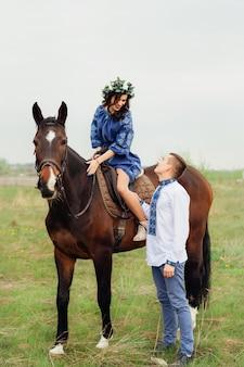 Vrouw in een mooie jurk en een krans op haar hoofd zit op een paard en kijkt naar de geliefde die naast haar staat