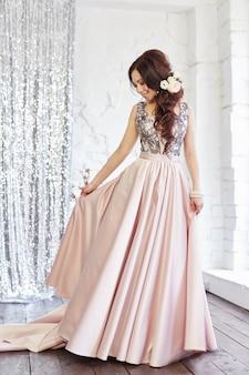 Vrouw in een mooie jurk in de buurt van een groot raam