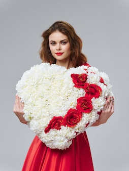 Vrouw in een mooie jurk met bloemen op 8 maart, geschenken bloemen lichte achtergrond valentijnsdag studio