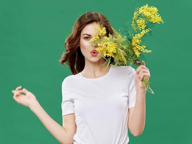 Vrouw in een mooie jurk met bloemen op 8 maart, geschenken bloemen lichte ruimte valentijnsdag