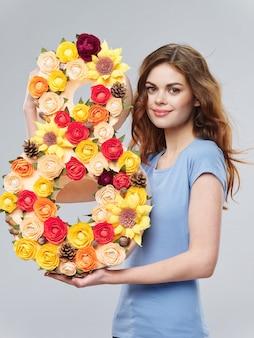 Vrouw in een mooie jurk met bloemen op 8 maart, geschenken bloemen valentijnsdag