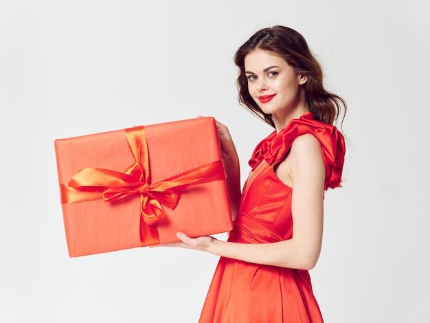 Vrouw in een mooie jurk met geschenk vakantie dozen in de studio, verkoop en feest