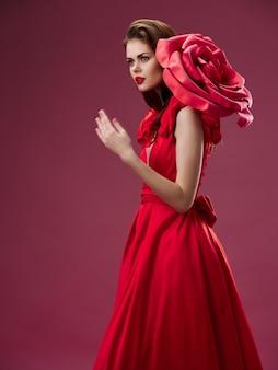 Vrouw in een mooie rode jurk met een roos en rozenblaadjes