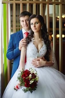 Vrouw in een mooie witte jurk en een man in een blauw pak knuffelen in de buurt van het raam