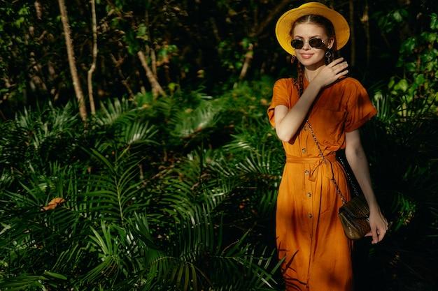 Vrouw in een oranje zomerjurk en hoed loopt in de natuur in de exotische jungle van het park