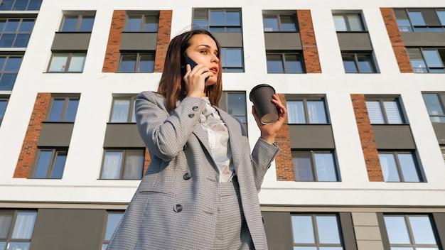 Vrouw in een pak drinkt koffie uit een plastic beker en praat aan de telefoon, tegen de achtergrond van een gebouw op een zonnige dag.