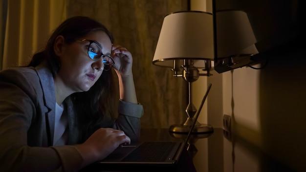 Vrouw in een pak in een donkere avond zit op een laptop, slow-motion