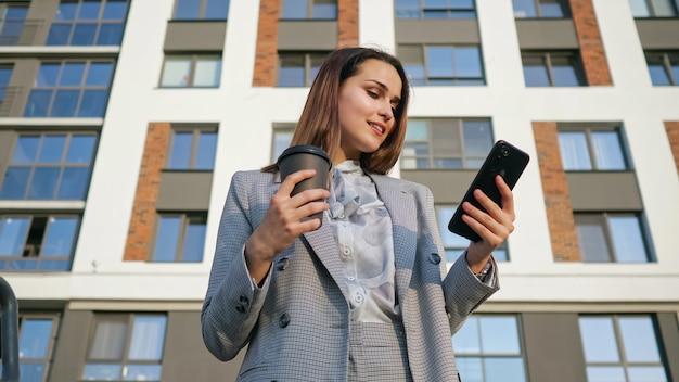 Vrouw in een pak kijkt naar de telefoon, terwijl ze een plastic beker op de achtergrond van een gebouw houdt.