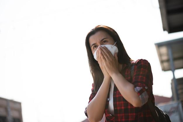 Vrouw in een pak met beschermende gezichtsmasker en hoest