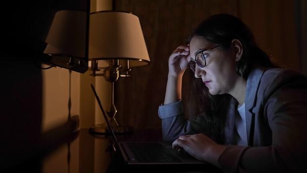 Vrouw in een pak zit op een donkere avond achter een laptop