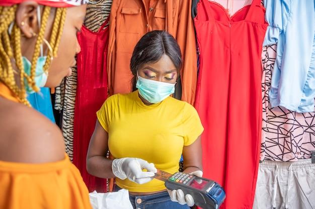 Vrouw in een plaatselijke winkel die een mobiel verkooppunt gebruikt