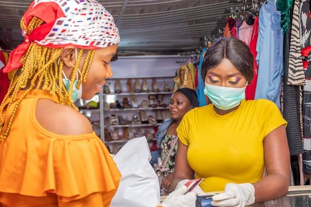 Vrouw in een plaatselijke winkel die met creditcard betaalt