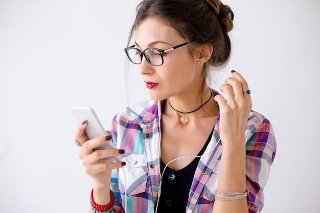 Vrouw in een plaidoverhemd in glazen die met hoofdtelefoons plaing